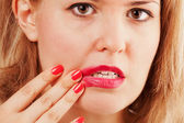 The girl smears lipstick on itself — Stock Photo