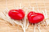 Candela rossa a forma di un cuore su una stuoia di bambù — Foto Stock