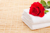 Stack of the white towel with red rose on the bamboo table — Stock Photo