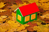 Toy house on autumn leaves background — Stock Photo