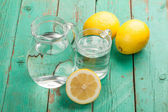 Glass and jar  with water and lemons — Stock Photo