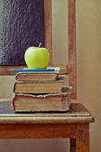 Green apple and old books on an old chair with vintage feel — Stok fotoğraf