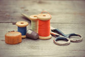 Tailor's tools - the old scissors, spools of thread, tape centim — Stock Photo
