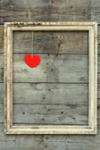 Vintage wooden frame with red heart on a grunge background — Stock Photo