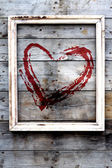 Wooden frame with red heart on a grunge background — Stockfoto