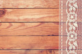 Beautiful white lace with floral ornament on wooden boards — Stock Photo