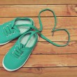 Stock Photo: Top view of pair of shoes with laces making heart shape on woo