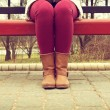 Young girl sitting on a bench in red pants and brown boots — Stock Photo