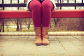 Young girl sitting on a bench in red pants and brown boots — Stockfoto