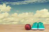 Sneakers and nectarine on a wooden table over cloudy sky — Stock Photo