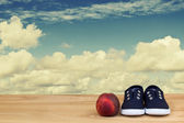Sneakers and nectarine on a background cloudy sky — Stock Photo