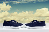 Blue sneakers on background cloudy sky — Stock Photo