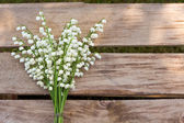 Lilly of the valley flowers on wooden background. — Stock Photo