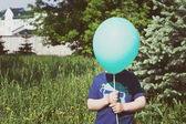 Child hiding behind the balloon — Stok fotoğraf