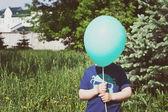 Child hiding behind the balloon — Stockfoto