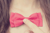 Stylish young girl holding a bow-tie near the neck — Stock Photo