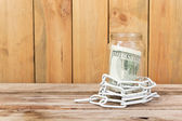 Money in a glass jar and chain on a wooden table — Stock Photo