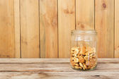 Cookies in glass jar on wooden table — Stock Photo