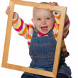 Laughing baby playing with picture frame — Stock Photo