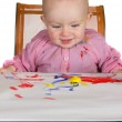 Happy baby girl playing with paint — Stock Photo