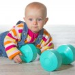 Whimsical baby girl with dumbbells — Stock Photo