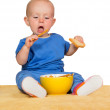 Stock Photo: Little baby eating biscuits