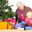 Gran and baby unwrapping Christmas gifts — Stock Photo
