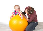 Devoted mother exercising her baby — Stock Photo