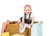 Laughing baby playing in a laundry basket — Stock Photo