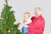 Grandmother and baby with Christmas tree — Stock Photo