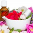 Essential oil and rose blossoms in mortar — Stock Photo