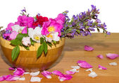 Wooden bowl with dog roses and sage flowers — Stock Photo
