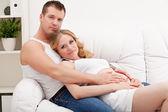 Happy pregnant family lies — Stock Photo