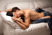 Young lovers kissing on the couch — Stock Photo