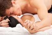 Sexy young couple kissing and playing in bed. — Stock Photo