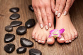 Relaxing pink manicure and pedicure with a orchid flower — Stock Photo