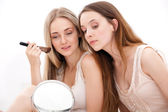 Group of women applying makeup on face — Stock Photo