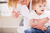 Doctor giving a child injection in arm — Stock Photo