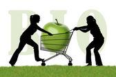 Mujeres luchan por un carrito de compra con una manzana bio — Foto de Stock