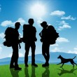 Stock Photo: Group of backpackers with dog on hill with mountains on back