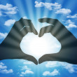 Heart made with fingers on blue sky background — Stock Photo