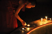 Young buddhist monk lighting candles — Stock Photo