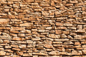 Old wall made of big and little yellow stones — Stock Photo
