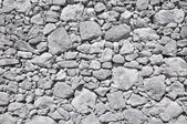 Grey old wall made of big and little stones — Stock Photo