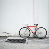 Modern red bicycle leaning on white wall — Stockfoto