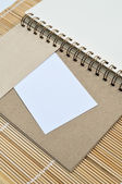 Blank notepad with a piece of paper on bamboo mat background — Foto de Stock