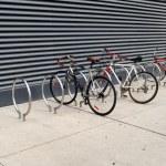 Three bikes are locked to sidewalk racks — Stock Photo #35021729
