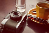 Empty cup of coffee and retro camera — Stock Photo