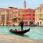 Venice: classic view of a romantic ride on a gondola boat in Grande Canale, near Rialto bridge, surrounded by historic buildings. — Stock Photo #24385585