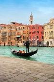 Venice: classic view of a romantic ride on a gondola boat in Grande Canale, near Rialto bridge, surrounded by historic buildings. — Stock Photo